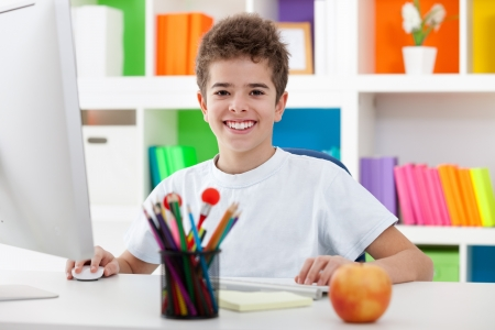 cute boy using a computer and smiling at home photo