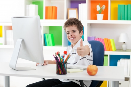schoolboys:  Boy sitting front of computer and showing thumb up Stock Photo