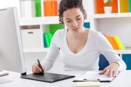 busy young woman sitting at desk using a graphic tablet Stock Photo - 19404916