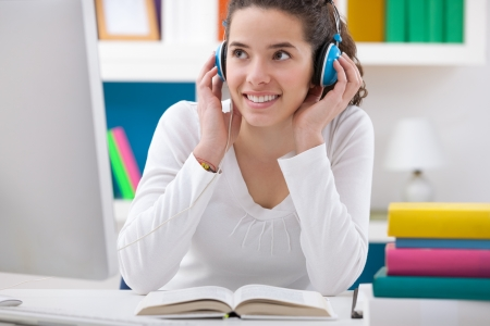 listen to music:  teenager girl listening music while sitting at a desk