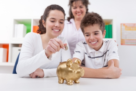 playing with money:  Happy mother with her children saving with piggybank