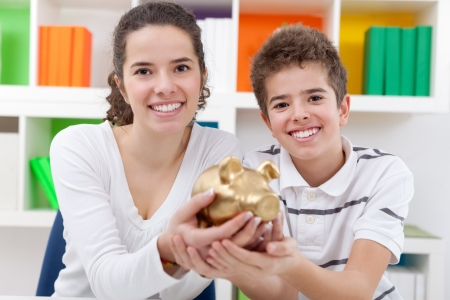Smiling two children holding  piggybank photo