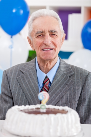 senior man having  birthday cake with a question mark candle photo