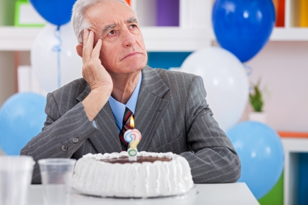 Senior men sitting front of cake birthday ask yourself how old am I Stock Photo