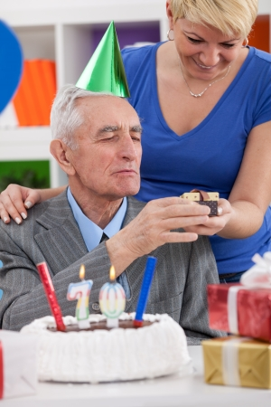 gives:  daughter gives father gift for 70th birthday Stock Photo