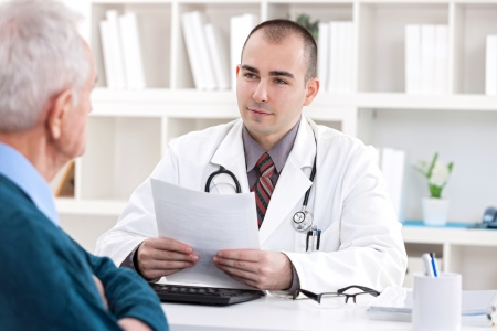 prescription:  Male doctor talking with senior  patient at office Stock Photo