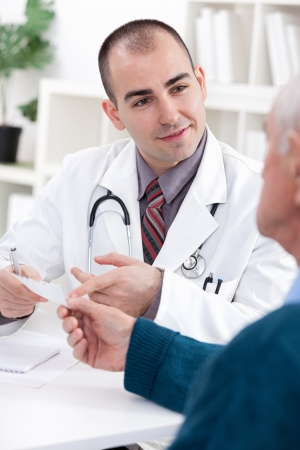 doctor giving pills: Handsome male doctor giving a prescription to his patient