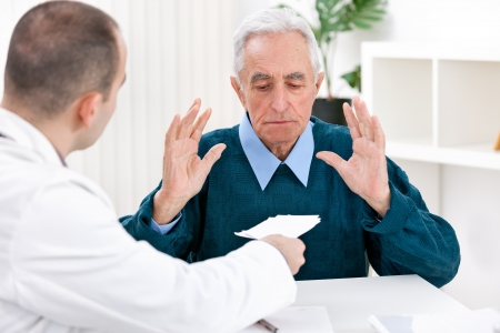 doctor giving pills:  Shocked senior patient with prescription at doctor's office
