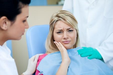 dent douleur: Jeune femme avec un mal de dents chez le dentiste