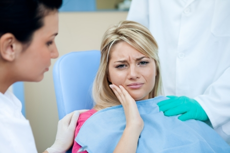 dolor de muelas: Mujer joven con dolor de muelas en el dentista