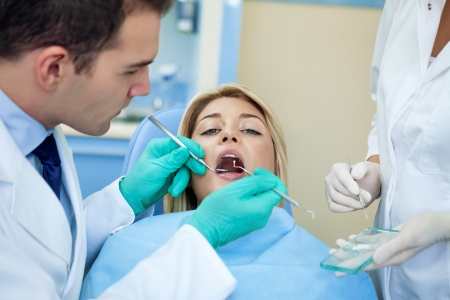 Dentist working on young female person photo