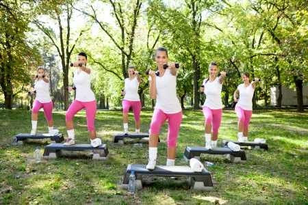cardiovascular exercising: Six young women doing exercises with dumbbells and steppers,  outdoor  Stock Photo