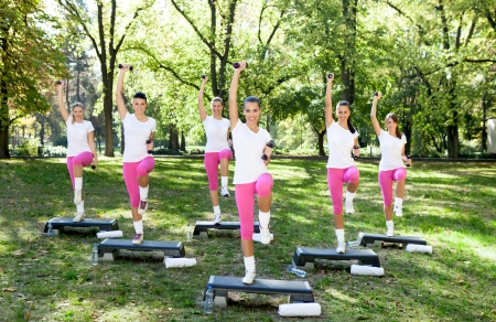 Energetic group of a young women doing fitness exercises outdoor on a sunny day photo