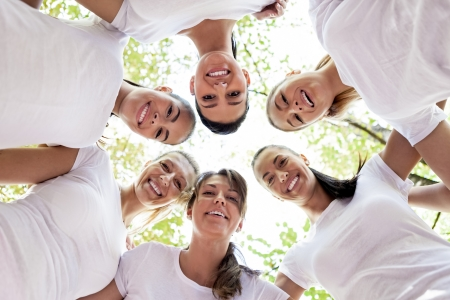 friendship circle: Group of women standing in the circle, smiling at the camera, low angle view  Stock Photo