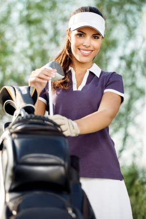 golfers: smiling young woman with golf equipment
