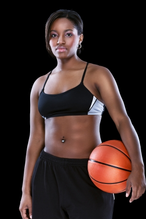 Attractive sporty afro woman posing with basketball over black photo