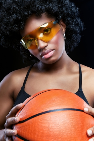 Fancy African woman with basketball and glasses photo