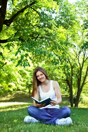 free time:  Free time of young woman in green park, reading book Stock Photo