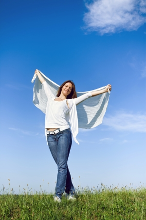 enjoy space:  outdoor portrait of beautiful girl with big piece of cloth under the blue sky