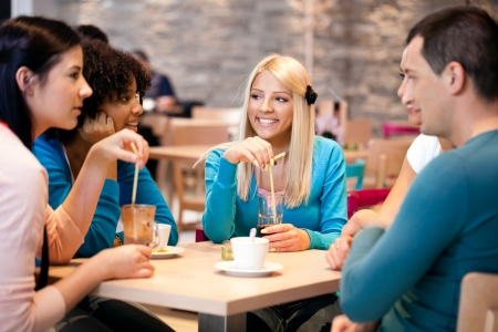 socializing:  young teenagers friends drinking coffee in a cafe Stock Photo