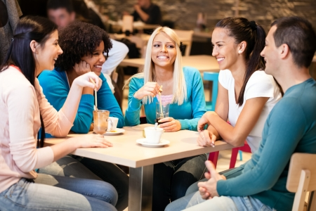 Young friends sitting on table in cafe Stock Photo - 19404559