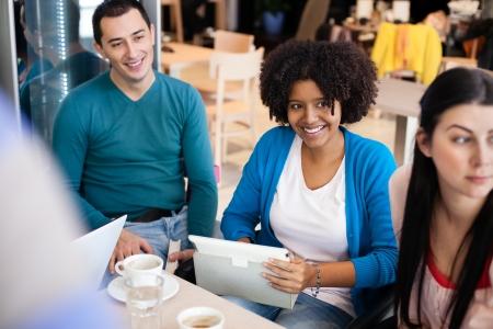 socializando: Estudiantes felices en café con la tableta