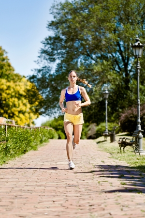 jogging track:  Young woman in sports clothing jogging in nature Stock Photo