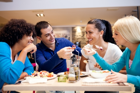 personas comiendo: Adolescentes felices que se divierten mientras que la comida en el restaurante