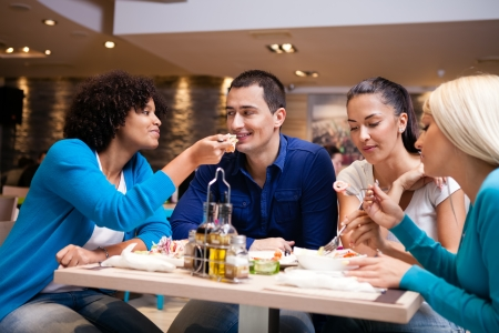 Four young friends eating in a restaurant or diner  photo
