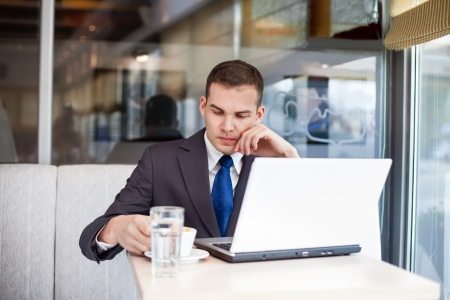 worried businessman sitting in front of laptop in cafe  photo