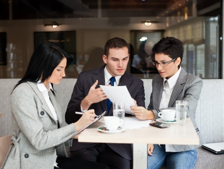 consulting team:  Young business people working over a paperwork and drinking coffee Stock Photo