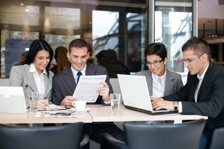 Gruppe von jungen Gesch�ftsleute sitzen an einem Tisch und diskutieren eine interessante Idee im Caf�