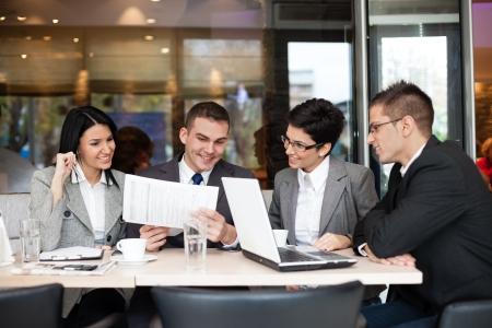 personas: Grupo de cuatro jóvenes empresarios reunidos en una mesa discutiendo una idea interesante en la cafetería Foto de archivo