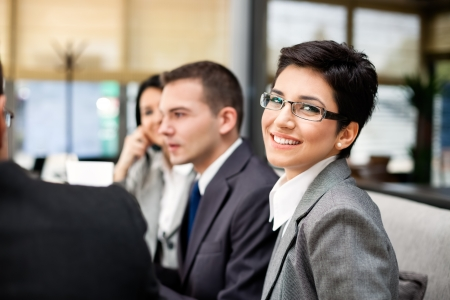 female lawyer: Closeup portrait of a smart young businesswoman smiling and her colleagues working   Stock Photo