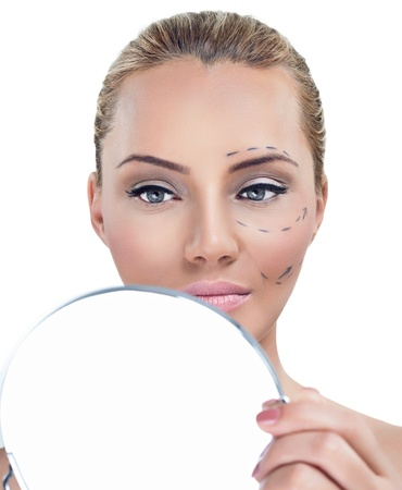 self operation: Cosmetic correction surgery, woman before plastic surgery looking in mirror Stock Photo