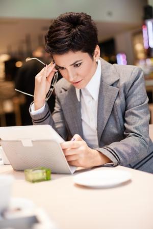 Upset businesswomen looking at tablet photo