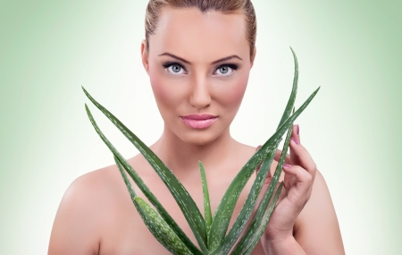Beautiful blond woman with healthy skin  and aloe  photo
