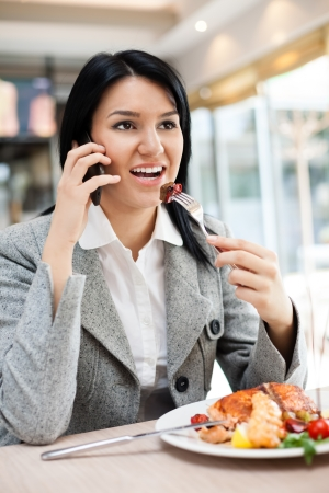 Young businesswomen eating in restaurant and talking on mobile phone photo