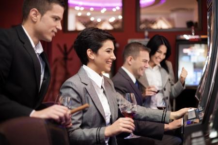 fichas casino: Personas Felicidad juegos de azar en el casino en las m�quinas tragaperras Foto de archivo
