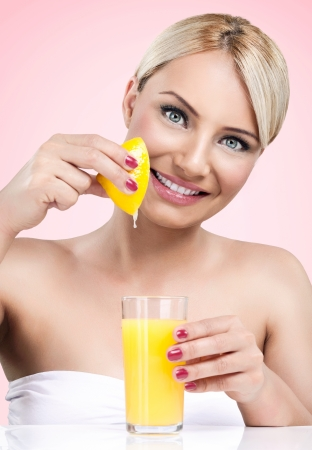 Woman  squeezes the juice from the lemon in glass photo