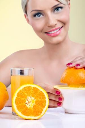 squeeze: Beautiful woman making orange juice with fresh orange  Stock Photo