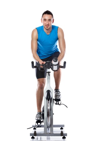 Young man exercising on a bike,  spinning exercise class photo