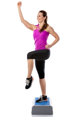 aerobics class:  Fitness girl is working out with stepper , isolated on white background