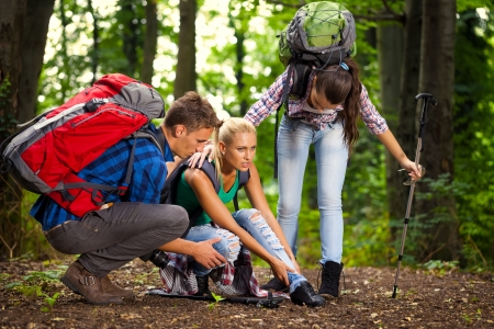 woman has sprained her ankle while hiking, her friends helps her