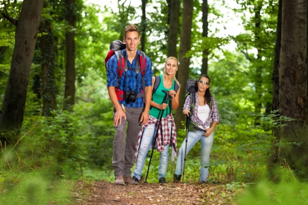 group of man and women during hiking excursion in woods, looking at camera and smiling photo