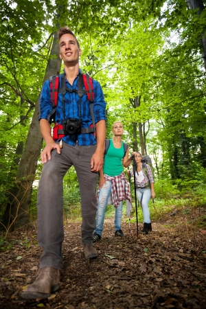 A happy man on a mountain trail with friends in the background photo