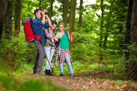navigating:  Group of hikers in forest searching right direction with map and binocular