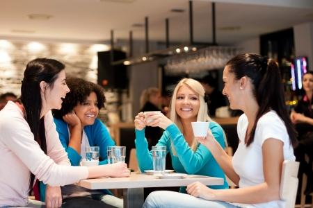 amigas conversando: grupo de mujeres jóvenes en el café, disfrutando de la discusión Foto de archivo