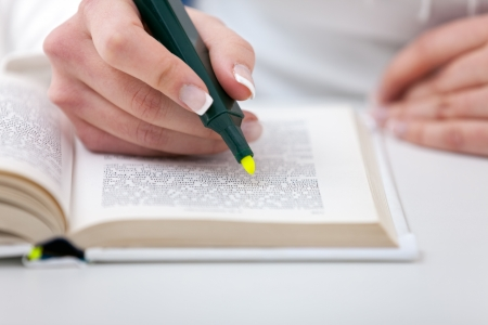 marked:  Highlighter  in female hand  marked text in book, education concept