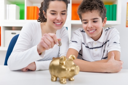 finance girl: Responsible brother and  sister putting money into piggy bank for future saving Stock Photo